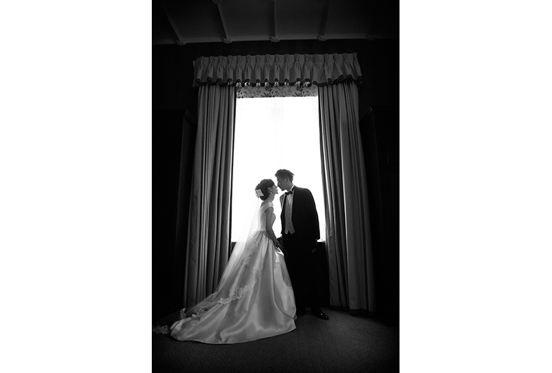 wedding couple kissing at the window